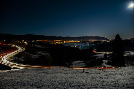 beautiful night panorama of the Asiago plateau, Veneto, Italy. Headlights trails of cars in the curves of the snowy road Stockfoto