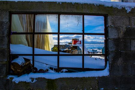 photo of a window with snow and an abandoned red bin on the Asiago plateau, Veneto, Italy.