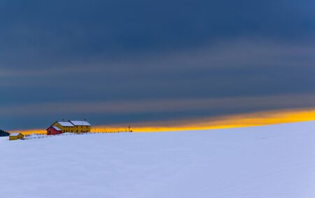 image of the yellow sunset from Porta Manazzo in winter with the yellow and red hut in the background on the Asiago plateau, Veneto, Italy.