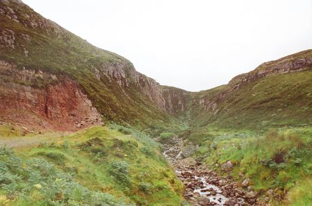 tumultuous stream descends downstream between two green Scottish hills