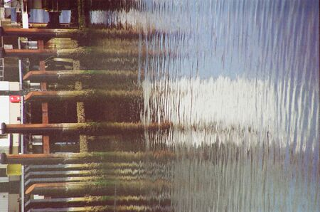 wooden poles are reflected on the icy north sea waiting for the fishing boats returning from the day of work