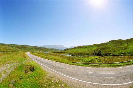 Asphalt road meanders along the Scottish hills on a cloudless summer day Banque d'images