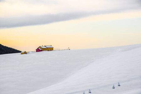 yellow and red hut at sunset above Val Formica covered in snow with the chairlift on the Asiago plateau, Vicenza, Italy