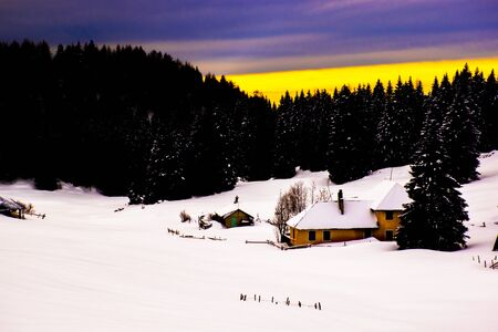 Alpine snowy landscape at sunset with hut, pine trees, clouds and mountain peaks, on the Asiago plateau in the province of Vicenza, Italy