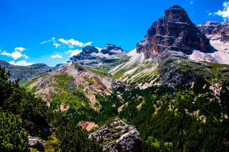 Blue sky with white clouds surround the pink peaks of the Cortina D'ampezzo Dolomites in Belluno, Veneto, Italy