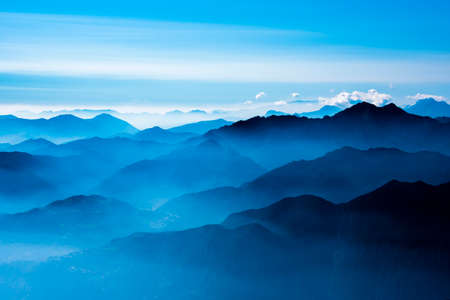 the peaks of the Alps around Lake Garda surrounded by fog with blue sky seen from Monte Altissimo, Trento, Italy Archivio Fotografico
