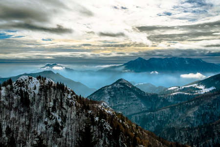 alpine landscape with snowy peaks and misty valleys, with menacing sky snow mountain peaks and blue layering in Tonezza, Vicenza, Italy
