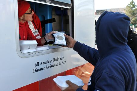 NEW YORK, NY - NOVEMBER 09: People collects hot lunches from a mobile Red Cross feeding unit in the Breezy Point part of Far Rockaway on November 9, 2012 in the Queens borough of New York City.