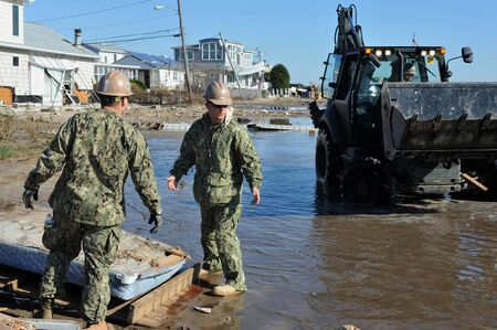 NEW YORK, NY - NOVEMBER 09: U.S. Marines from the 8th Engineer Support Battallon out of Camp Lejeune, North Carolina, move a debris and parts of destroyed houses in the Breezy Point part of Far Rockaway on November 9, 2012 in the Queens borough of NY.