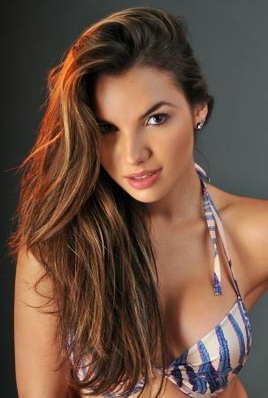 Pretty latino swimsuit fashion model posing in the studio