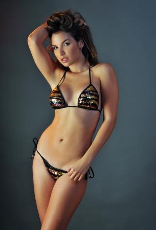 bikini wear: Pretty latino swimsuit fashion model posing in the studio