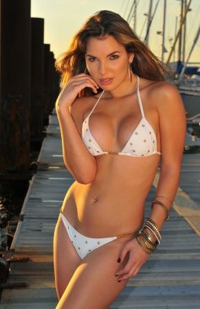 Pretty latin swimsuit fashion model posing sexy at boat marina location