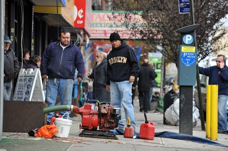 BROOKLYN, NY - NOVEMBER 01: Peoplepumping water out buildings at the Brighton Bwach neighborhood due to impact from Hurricane Sandy in Brooklyn, New York, U.S., on Thursday, November 01, 2012.  
