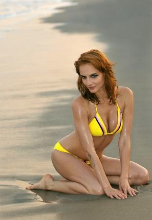 Jonge roodharige model zittend op hij strand wal in gele bikini