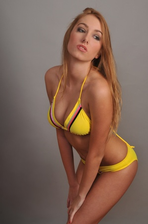 hat nude: Sexy blond woman wearing yellow bikini  posing in the studio