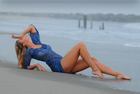 Fashion model posing on the beach wearing blue mini dress photo