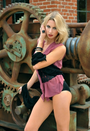 abandoned car: Model posing sexy in front of old rusty gear metallic background
