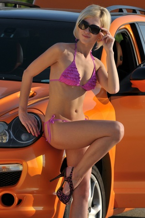 Young sexy girl posing by metallic orange sport car