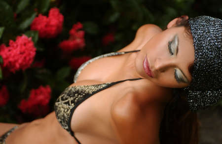 Exotic looking model posing in bikini at tropical forest with red flowers on background photo