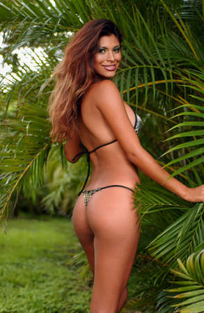 Exotic looking model posing in bikini at tropical forest with palm trees on background Stock Photo