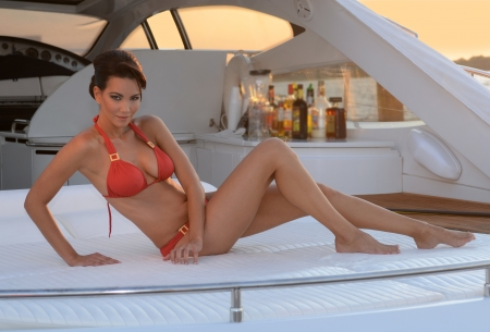 Brazilian model sitting pretty at the deck of 62 ft  motor boat, wearing red designer