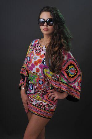 아름 다운 젊은 갈색 머리 소녀 짧은 드레스와 선글라스를 착용 한 스튜디오에서 카메라에 예쁜 포즈