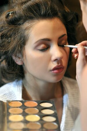 palitra: Make up Artist applying eye shadow for young female  Stock Photo