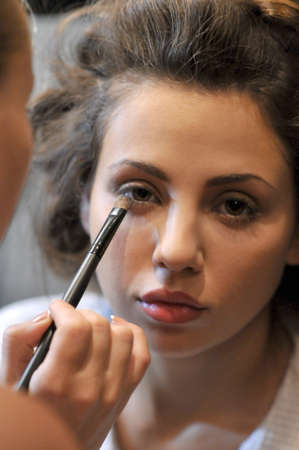 make up artist: Make up Artist applying eye shadow for young female  Stock Photo