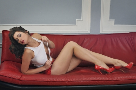 Sexy brunette girl with long legs posing at red sofa wearing red short, ripped off t-short and pumps photo