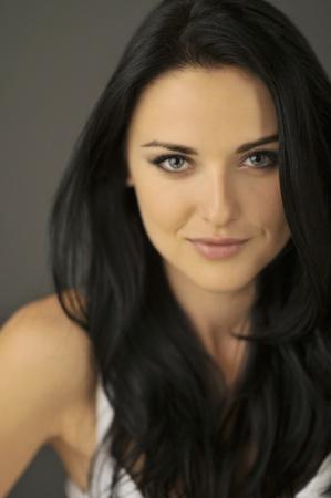 필드의 푸른 눈을 얕은 깊이와 매력적인 미소 젊은 갈색 머리 여자는 눈에 초점