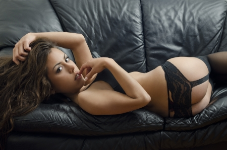 Portrait of young brunette woman posing sexy in lingerie at black leather sofa love seat Stock Photo - 18325848