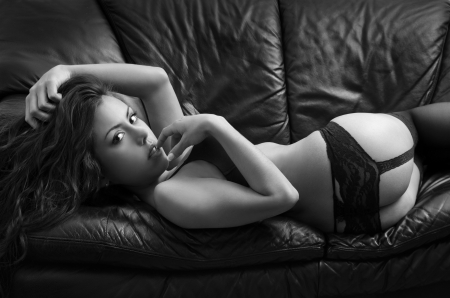 Portrait of young brunette woman posing sexy in lingerie at black leather sofa love seat