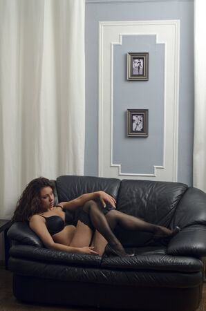 A young brunette woman posing sexy in lingerie at black leather sofa love seat photo