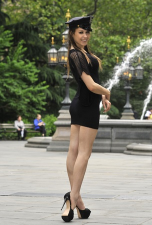 Fashion model posing in short black dress and NYPD police hat in front of fountain in New York City park photo