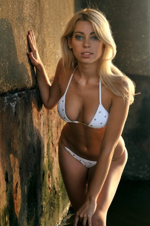 Young blond woman in white bikini against a rusty concrete wall on the beach