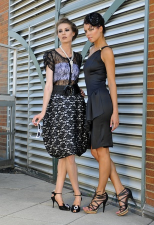 Two fashion models posing pretty outside in couture dresses photo