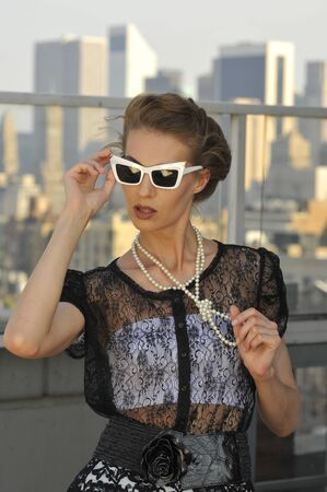 Fashion model wearing couture clothes and accessories posing in front of city view  Stock Photo