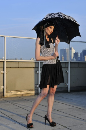Fashion model wearing couture clothes and holding umbrella photo