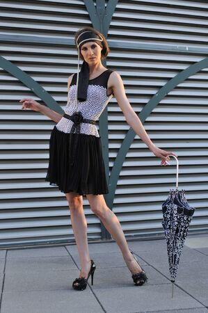 Fashion model posing outside wearing couture designer s dress and holding umbrella photo