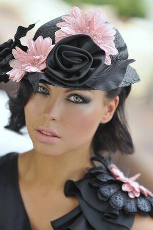 Portrait of seductive brunette fashion model wearing designer s hat with flowers photo