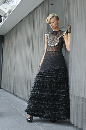 Fashion model wearing long couture black dress and gloves photo