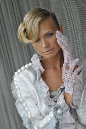 Portrait of blond fashion model wearing couture clothes and gloves photo
