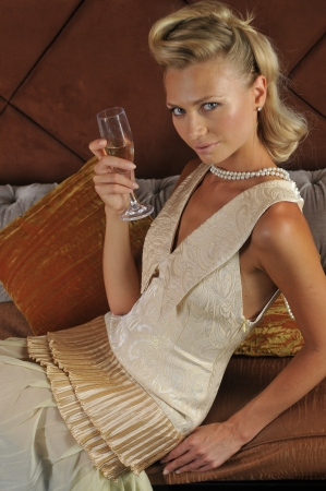 Beautiful blond model with a glass of champagne posing pretty on the sofa in restaurant lounge interior wearing couture dress photo