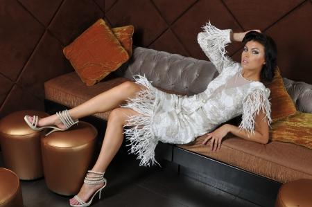 Fashion model poseren op de slaapbank in het restaurant lounge interieur draagt couture ontwerper jurk