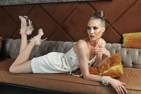 Fashion model posing pretty on the sofa in restaurant lounge interior wearing couture dress and high heels photo