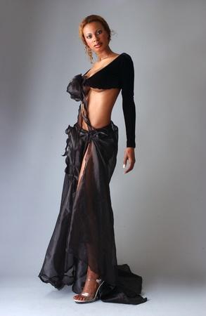 Prachtige Afrikaanse Amerikaanse model stellen het dragen van modieuze jurken