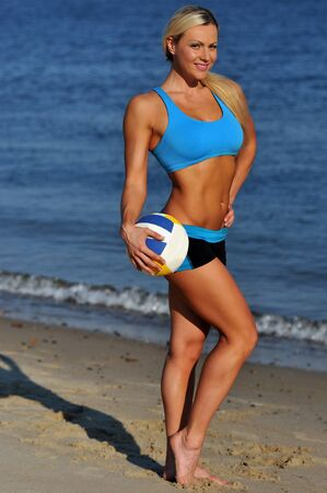A sporty fit woman in her fitness clothes holding a volleyball ball on the beach photo