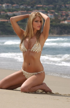 Young blond girl on the beach of Redondo Beach,CA posing pretty in bikini barefoot  Stock Photo