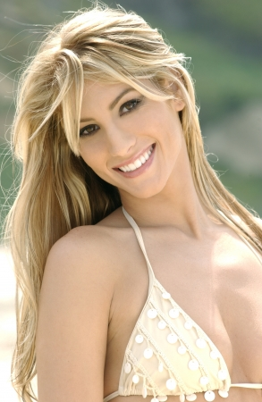 Portrait of beautiful young woman wearing bikini on the beach and smiling to the camera  photo