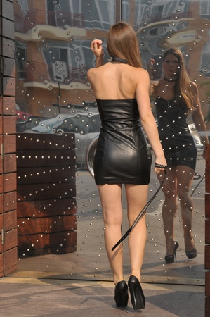 Attractive girl in leather mini dress posing sexy in front of reflective metal door photo